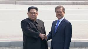 Kim and Moon shake and hold hands